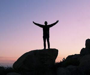 Man on top of rock with arms outstretched to the sky